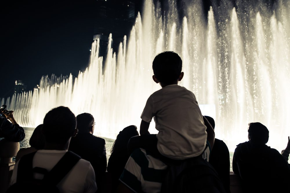 A young child sits on the shoulders of his parent while watching like lit up fountain on the Las Vegas strip