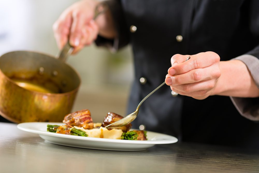 A chef spoons sauce over a dish